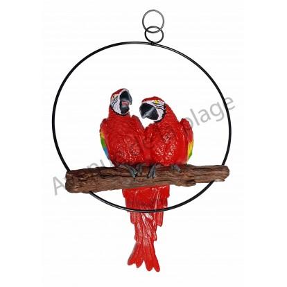 Couple de perroquets rouges sur perchoir à suspendre.